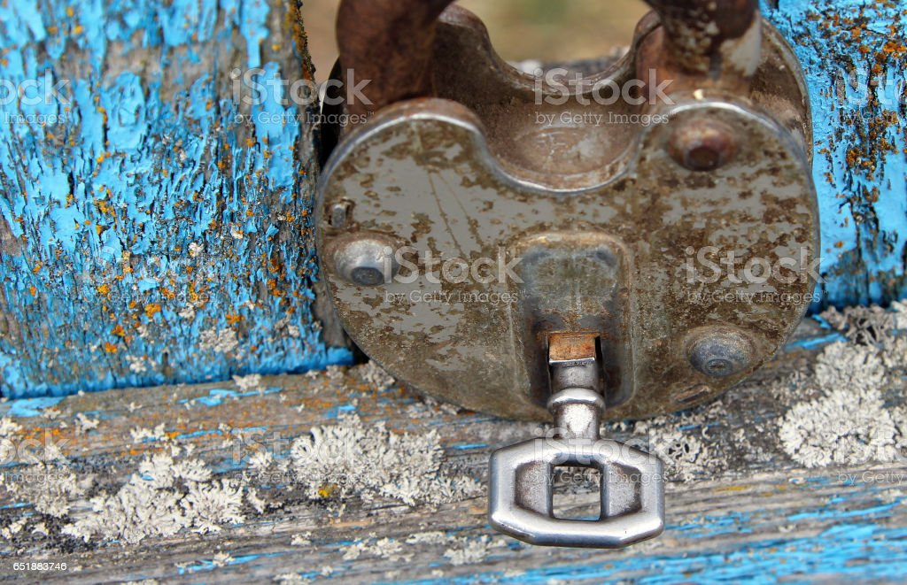 Rusty lock with a key on a blue wooden door stock photo