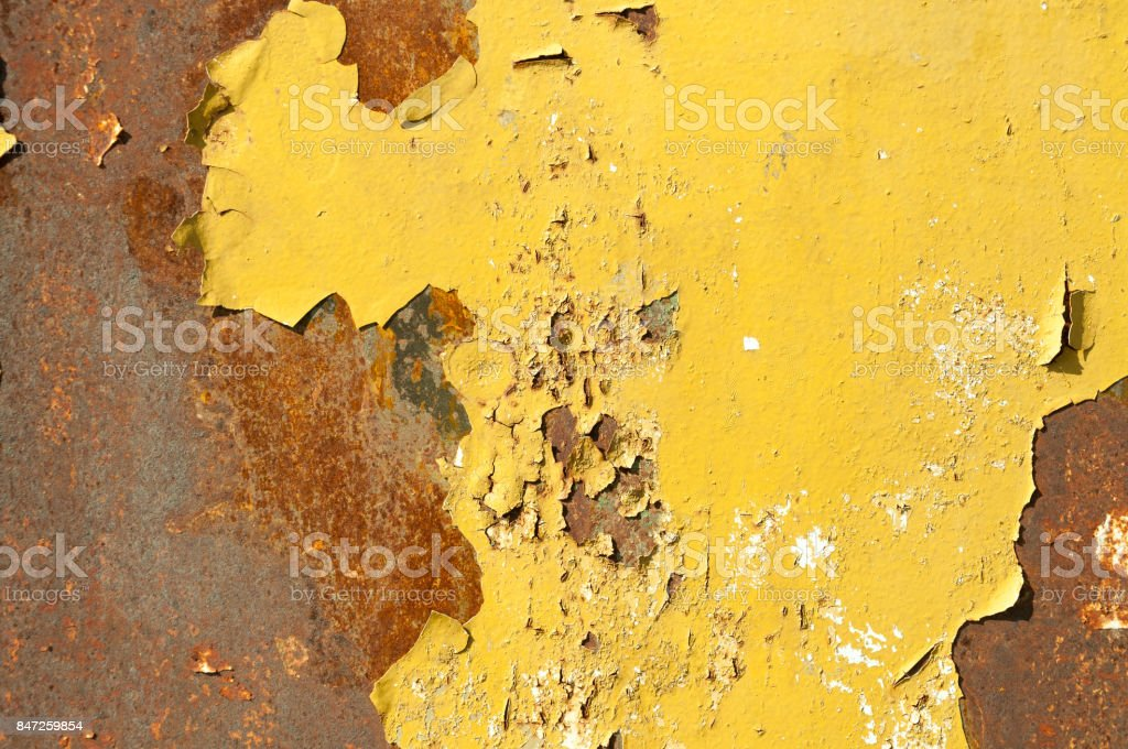 Rusty metal background surface with pealing yellow paint stock photo