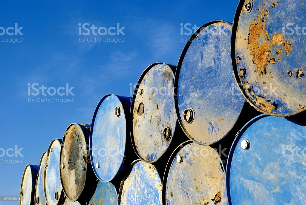Rusty metal barrels stacked in rows stock photo