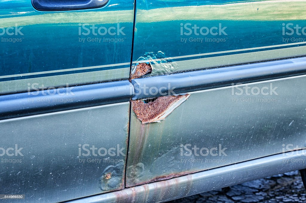 Rusty Metal Corrosion Holes On Damaged Car Rear Door stock photo