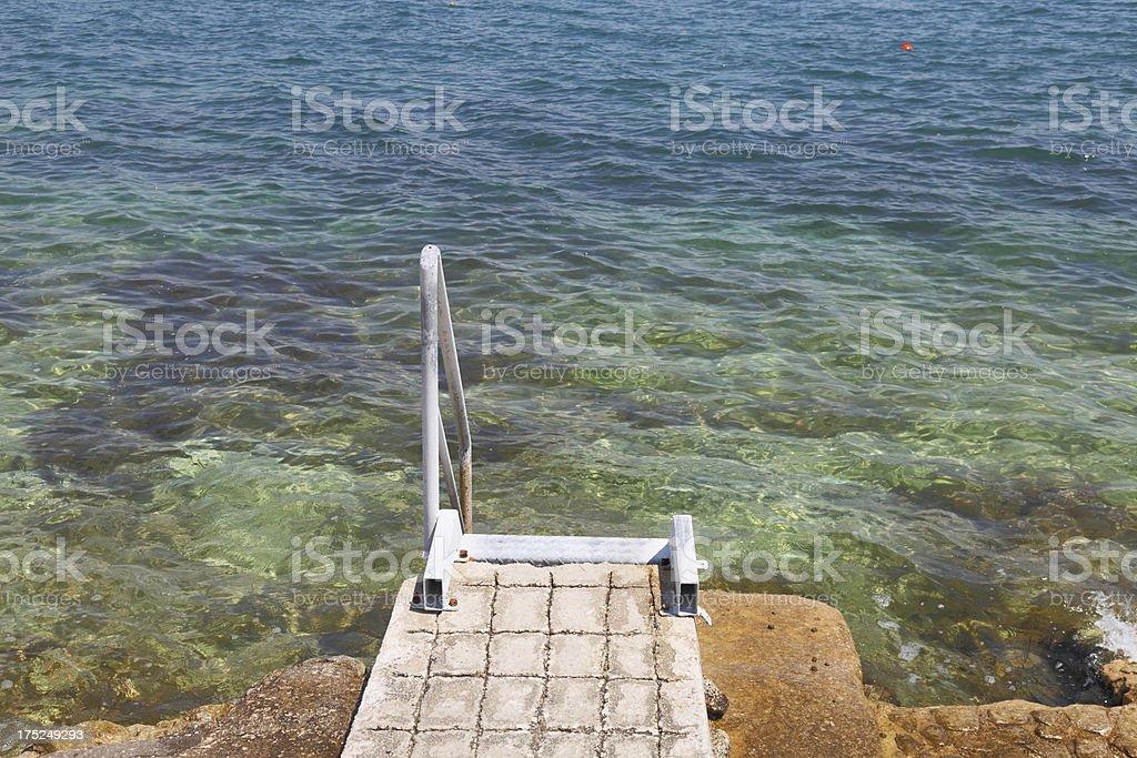 rusty metal ladder at blue mediterranean beach Trogir Croatia royalty-free stock photo
