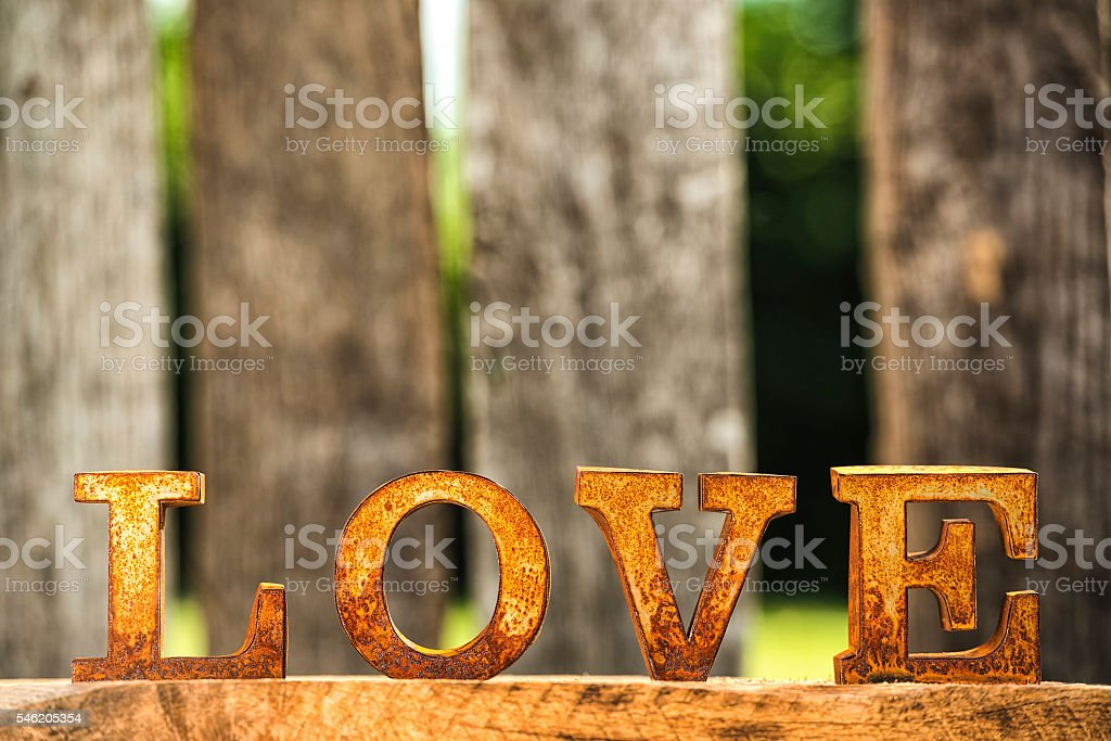 Rusty metal letters spelling LOVE against old wooden fence stock photo