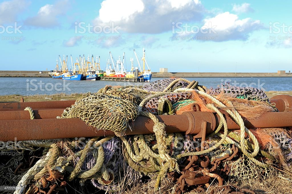 Rusty metal parts and fishing nets in a fishing harbour. stock photo