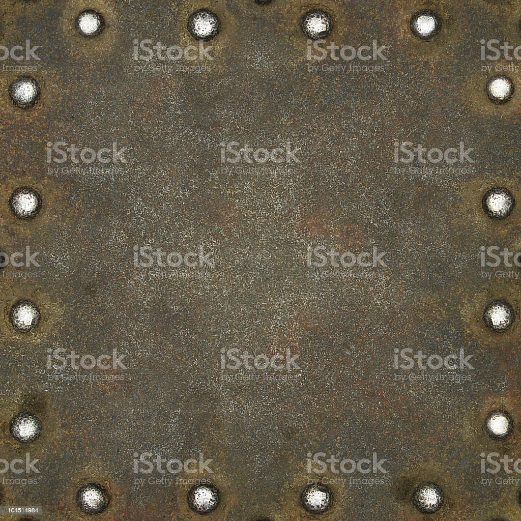 Rusty metal plate secured with shiny rivets royalty-free stock photo