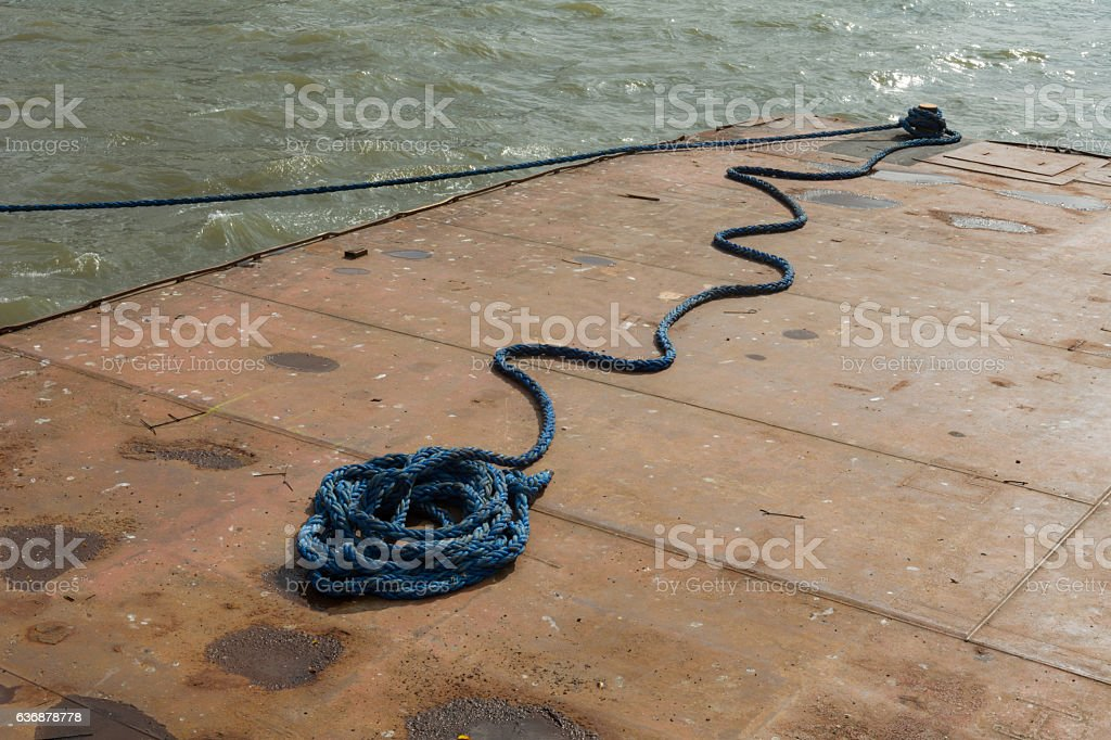 rusty metal pontoon on river with blue rope on deck stock photo