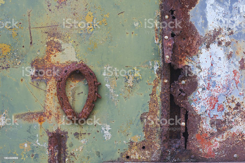 Rusty metal surfaces with a horseshoe royalty-free stock photo