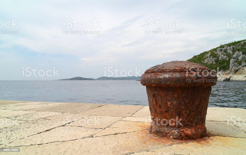 Rusty mooring bolard stock photo