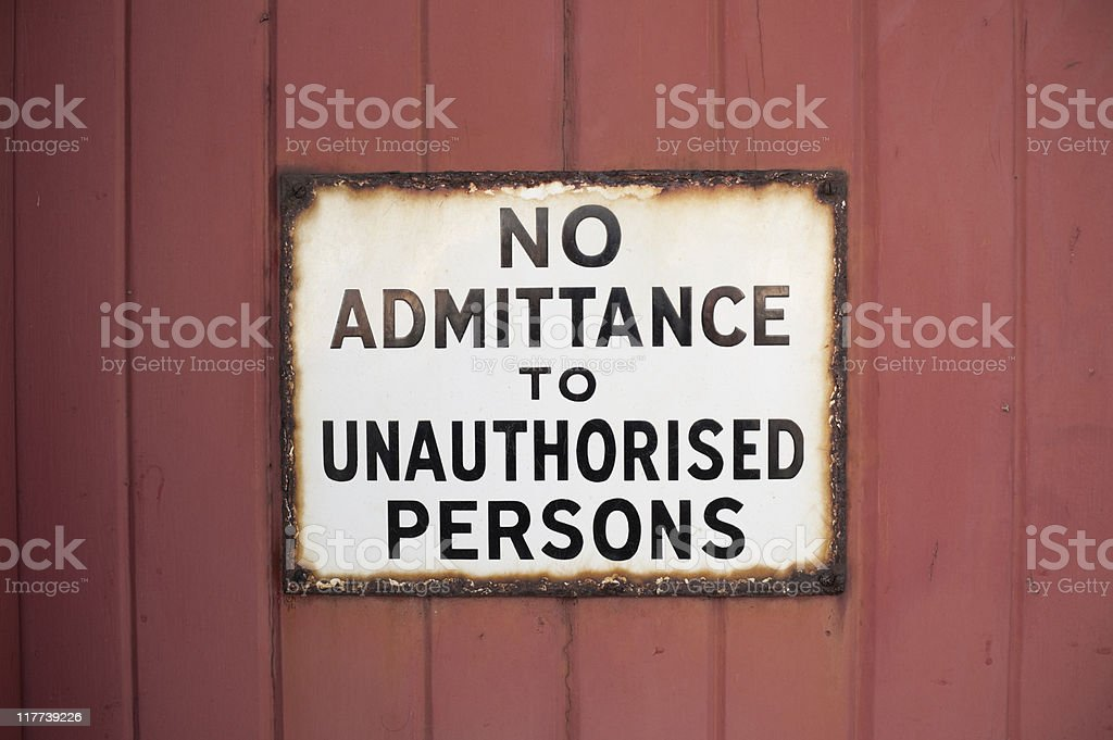 rusty no admittance to unauthorised persons sign on red stock photo