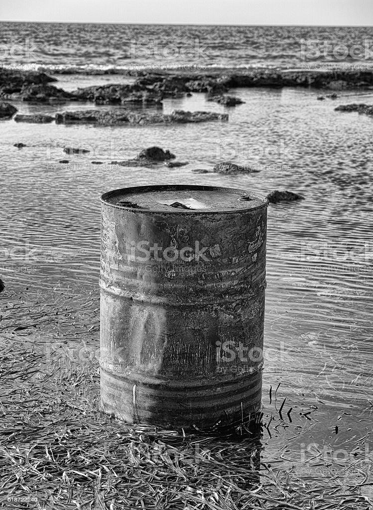 Rusty oil barrel near the shore of the sea stock photo