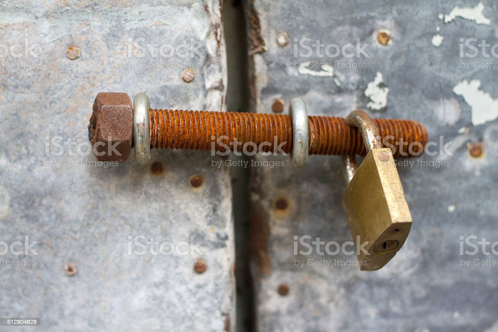 Rusty Old Bronze Padlock on Old Gray Tin Door (Close-Up) stock photo