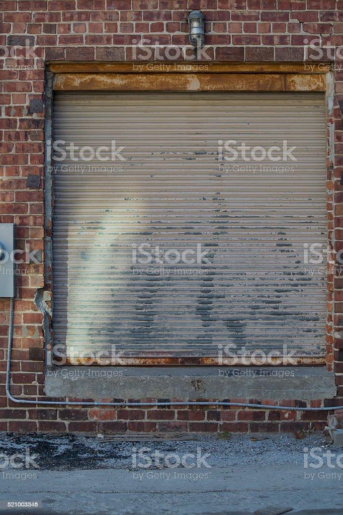 Rusty old garage door with brick wall stock photo