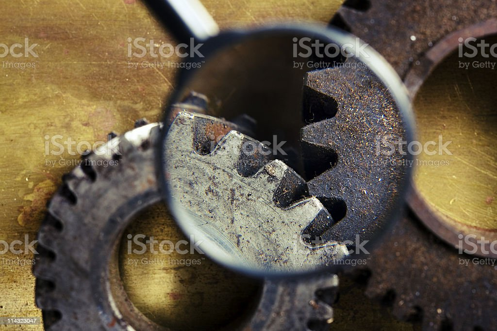Rusty old gears with magnifying glass stock photo