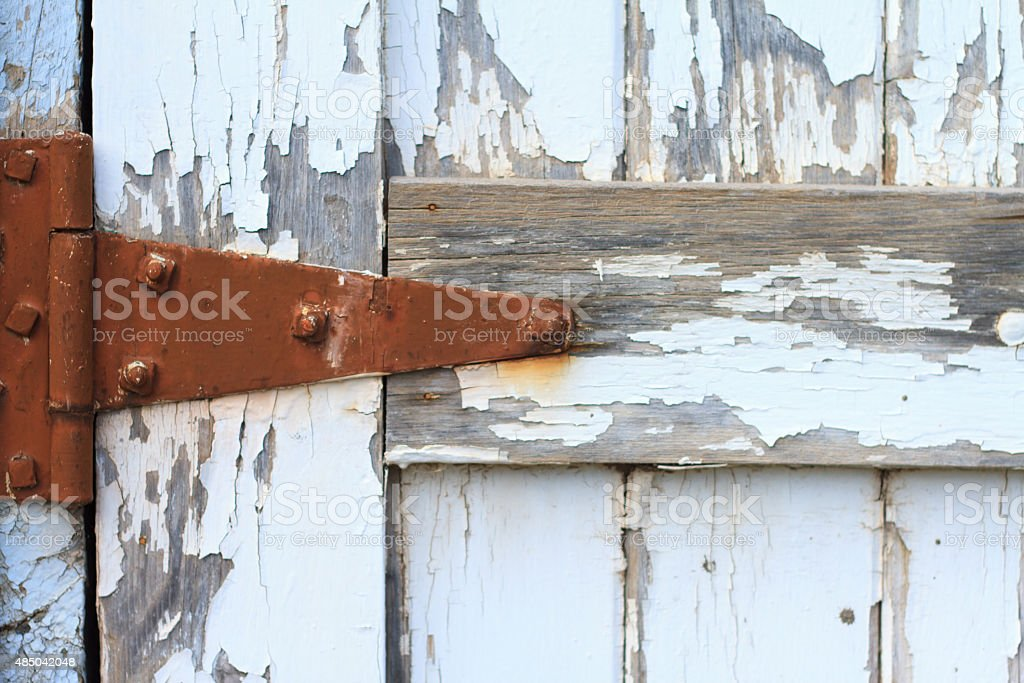 Rusty Old Hinge on Distressed White Door (Close-Up) stock photo