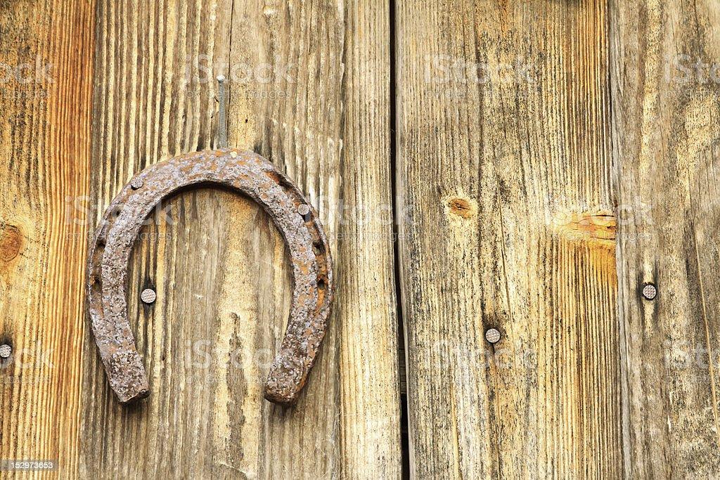 Rusty Old Horseshoe Mounted On Textured Wood Planks stock photo