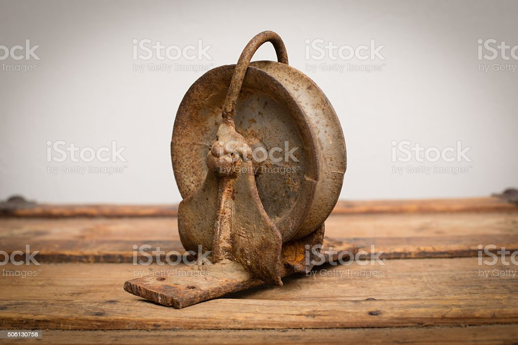 Rusty Old Metal Industrial Pulley on Wood Trunk stock photo