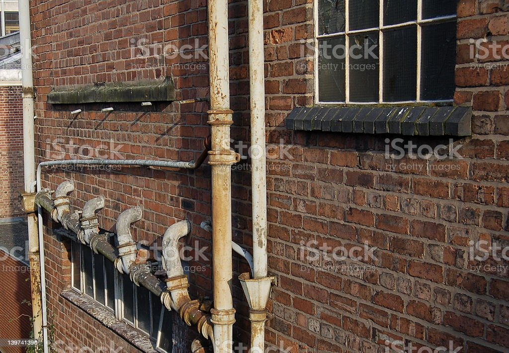 Rusty Old Pipes In A Brick Wall stock photo
