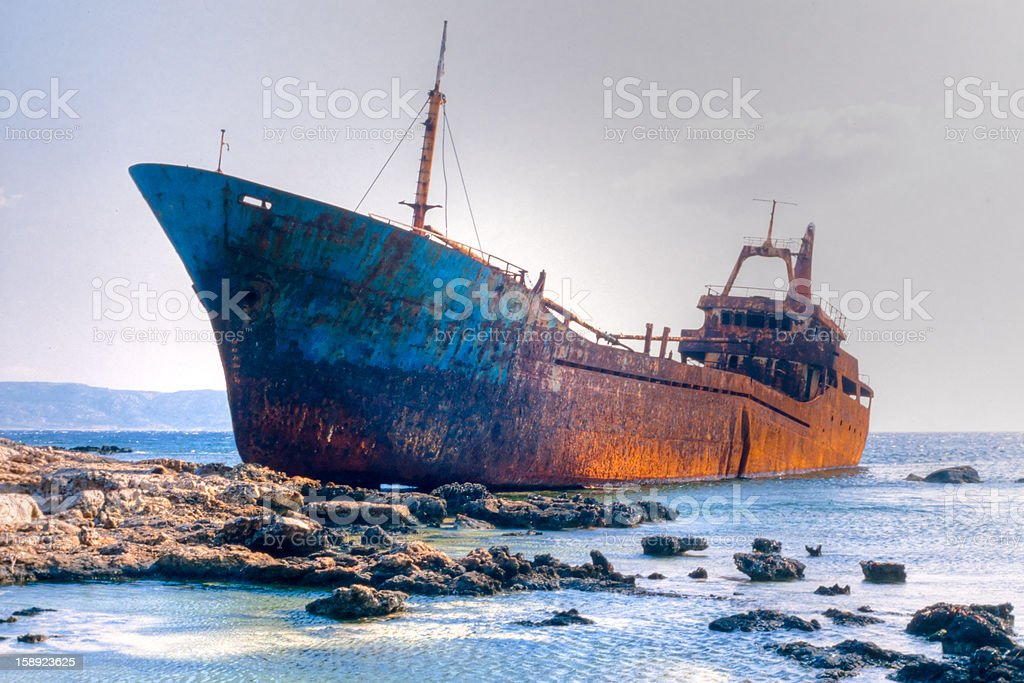 Rusty old shipwreck aground  on rocky reef stock photo