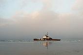 Rusty old shipwreck ruins, beach reflection, coast Sakhalin island, Russia