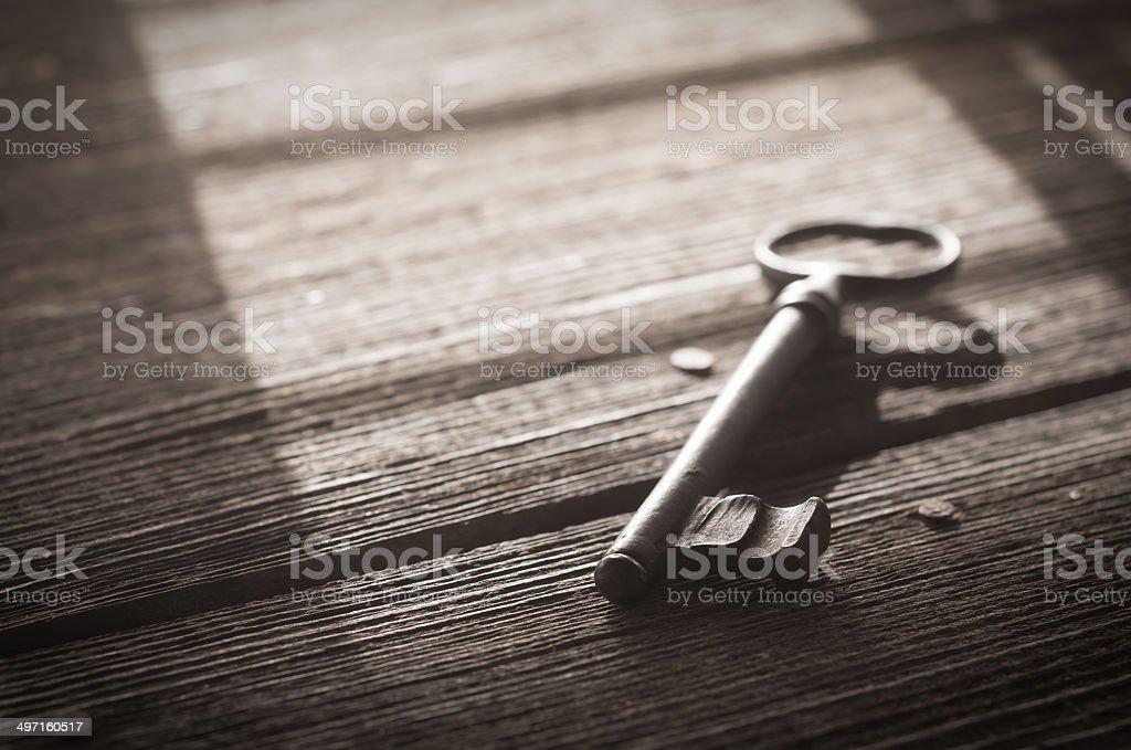 Rusty Old Skeleton Key on Barnwood With Window Light stock photo