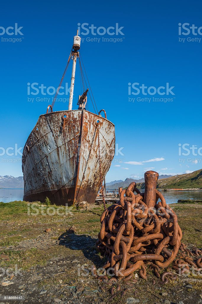 Rusty old whaler chained to iron post stock photo