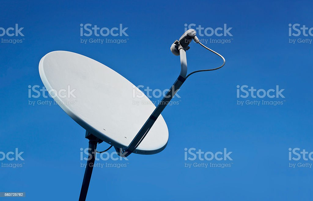 Rusty old white satellite dishes on blue sky background stock photo