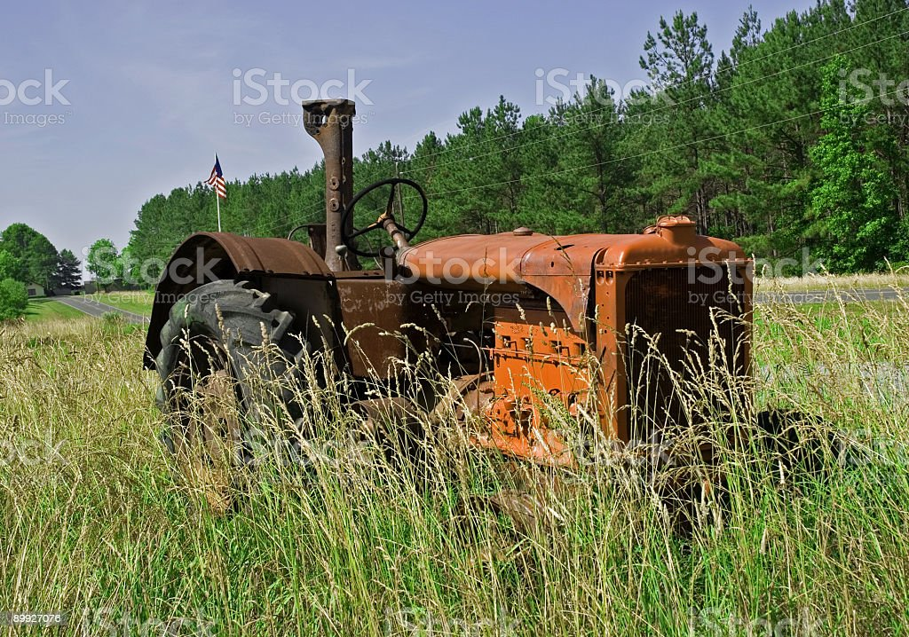 Rusty Orange Tractor In Tall Grass royalty-free stock photo