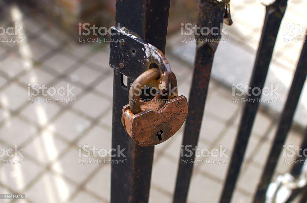 Rusty padlock hanging on a metal gate stock photo