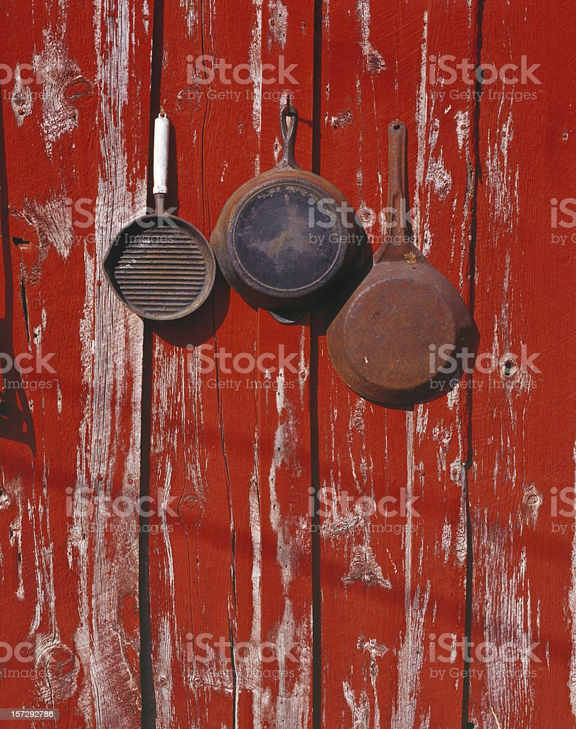 Rusty Pans, Cowboy Skillets, Red Painted, Weathered Barn Wall, Cooking royalty-free stock photo