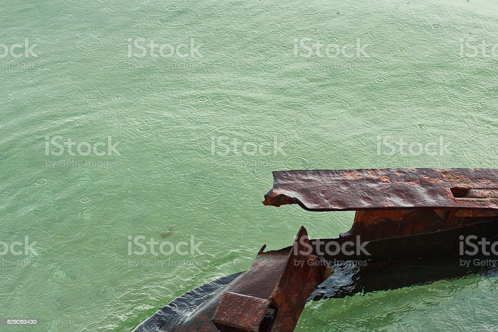 Rusty remains of a bridge in the water during rain stock photo