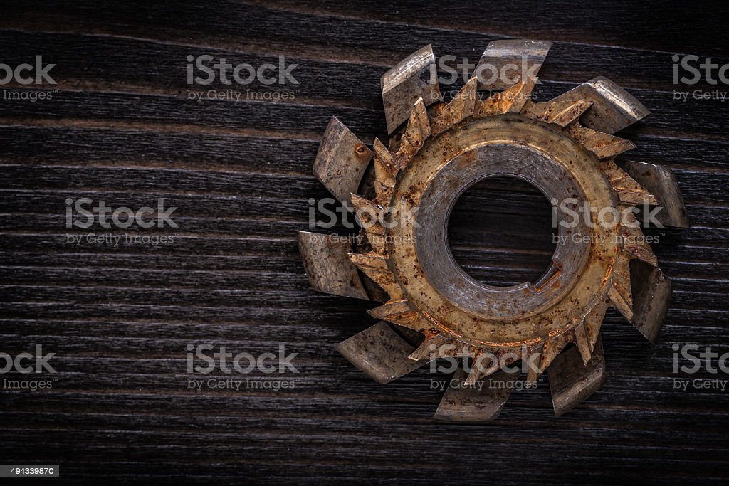 Rusty rotary cutter on vintage wooden background construction co stock photo