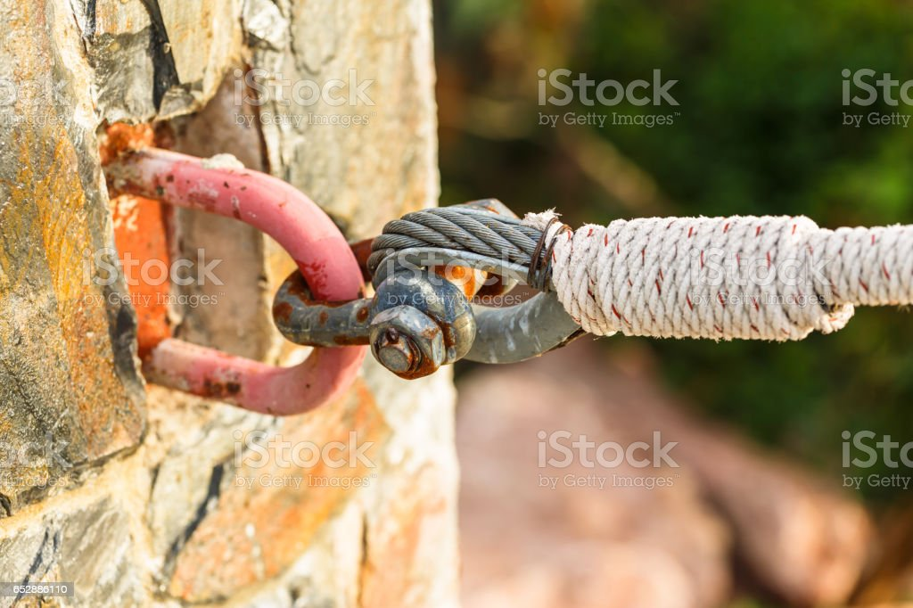 rusty shackle connect the sling and rope tied knot in nature background stock photo