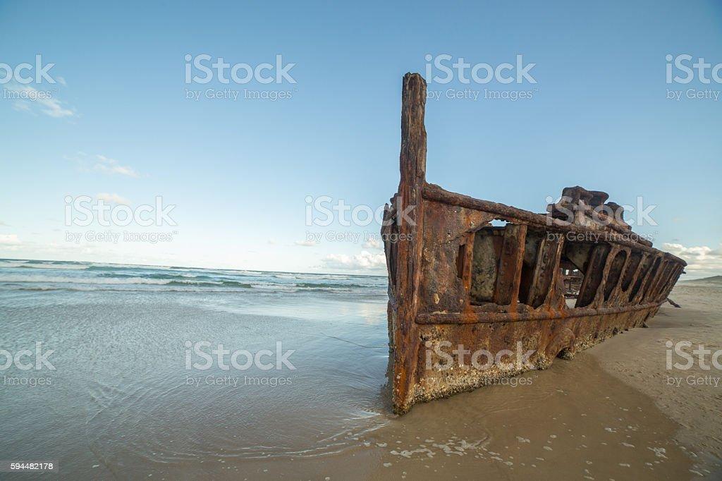 Rusty shipwreck on beach stock photo