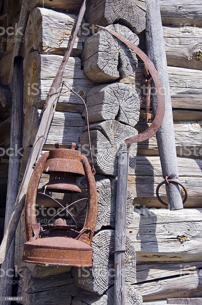 rusty sickle and kerosene lamp on old farm wall royalty-free stock photo