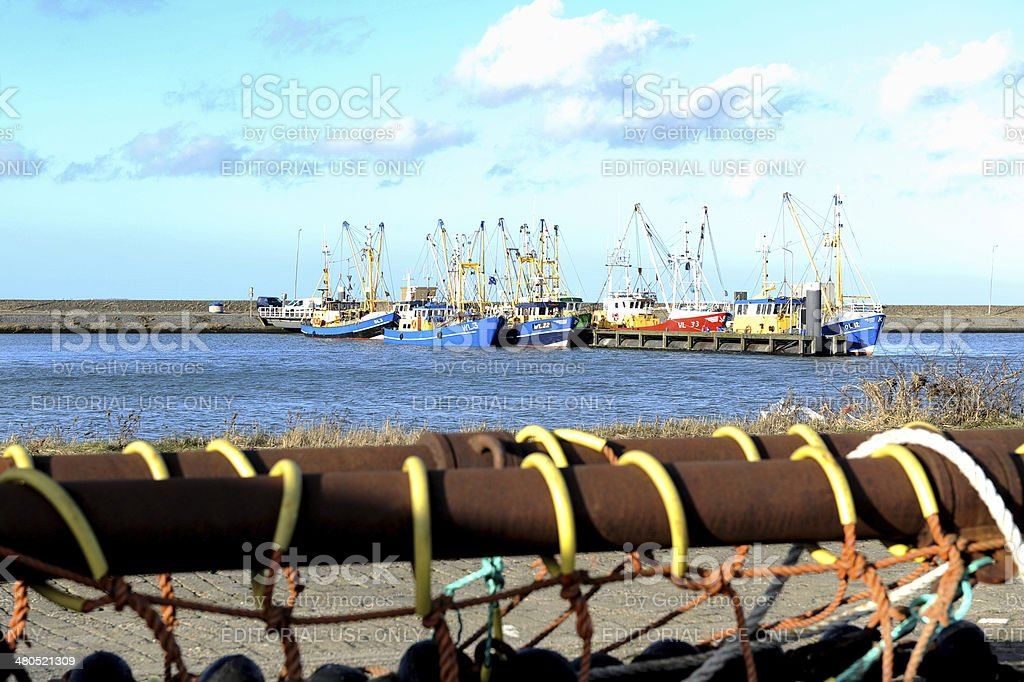 Rusty spar and fishing nets with ships in the background stock photo