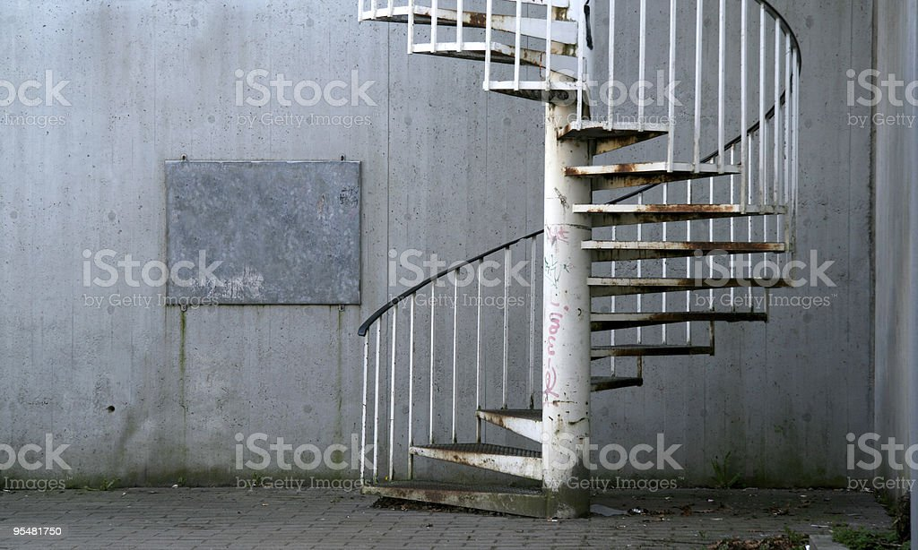 Rusty spiral staircase, frame and concrete wall royalty-free stock photo