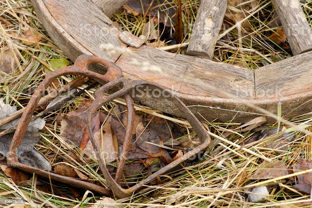 rusty stirrups lying next to a wooden wheel stock photo