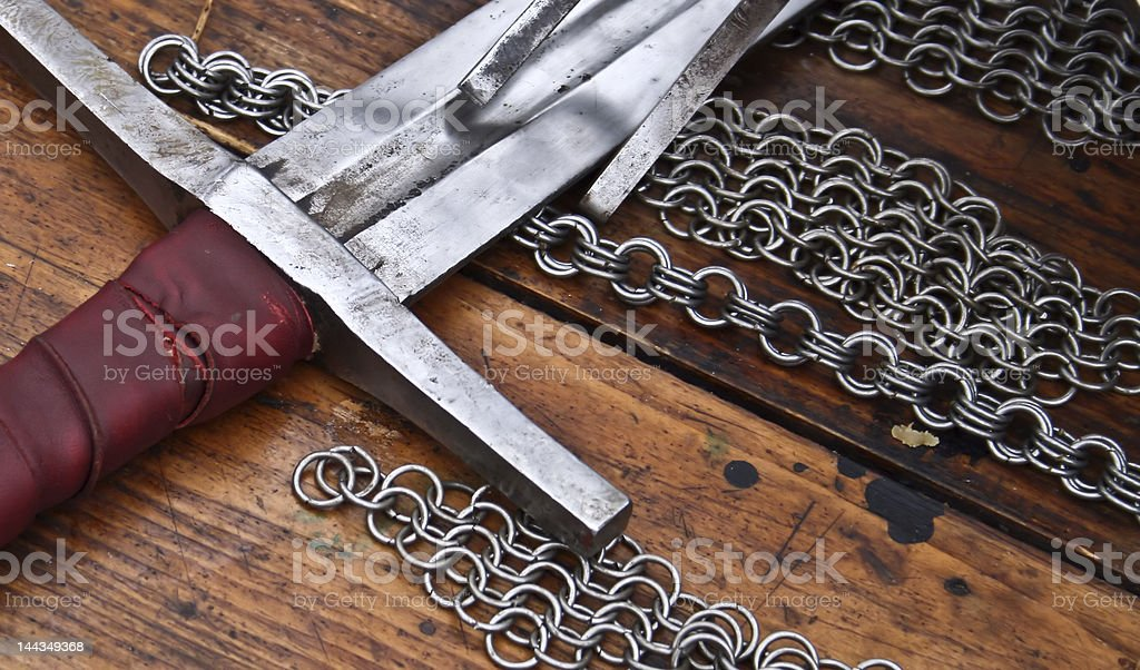 Rusty sword sitting on chainmail and wooden surface stock photo