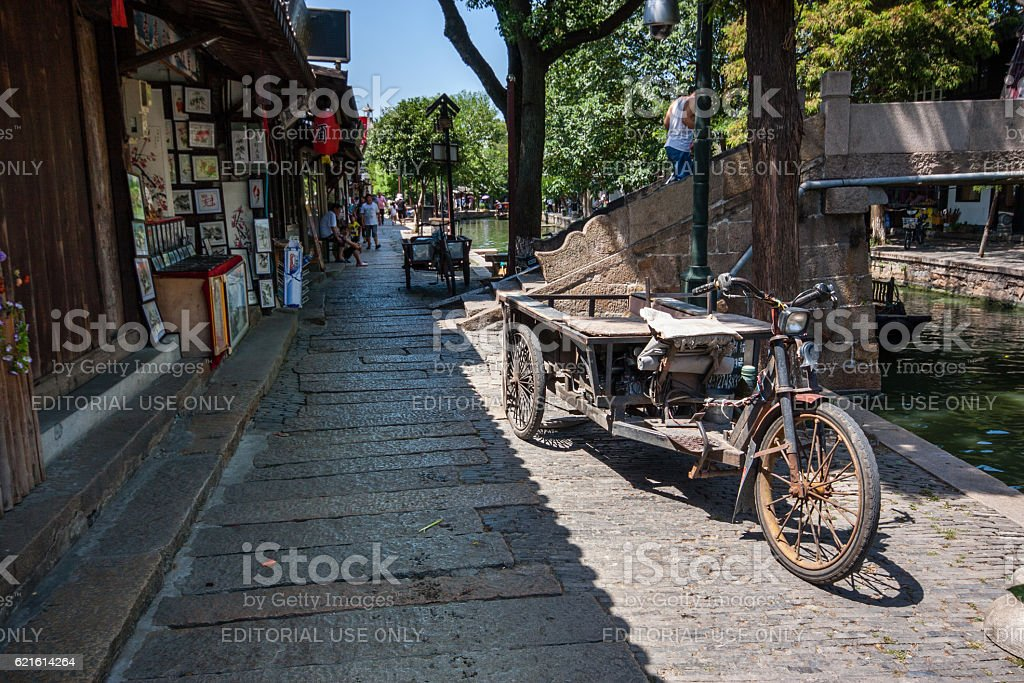 Rusty three wheeled freight electric bike parked on canal embankment stock photo