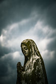 Rusty Virgin Mary statue with dramatic storm clouds