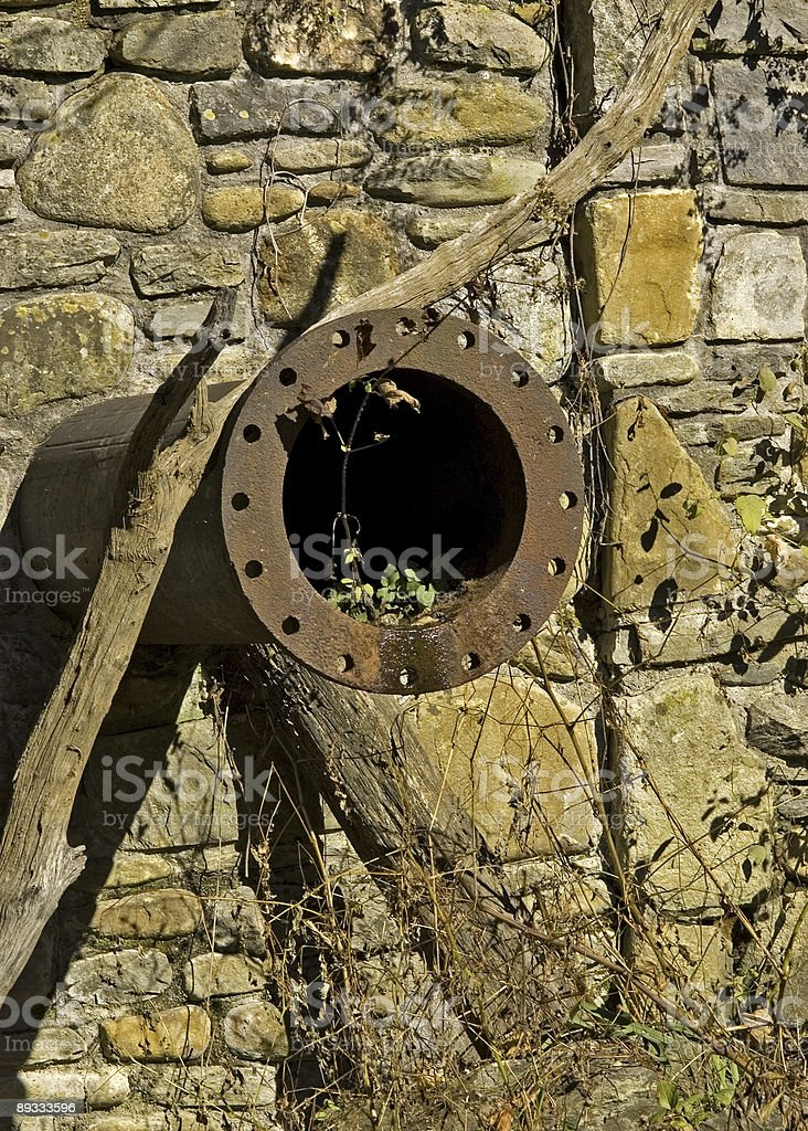 Rusty Water Pipe in a Stone Wall royalty-free stock photo