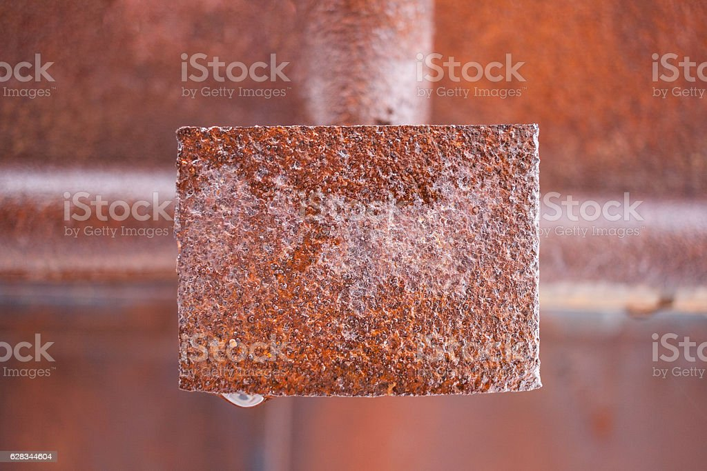 Rusty wet metal rectangular plate in middle of frame. stock photo