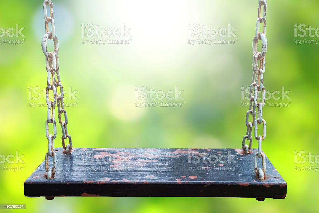Rusty wood swing and blurry green backgrounds royalty-free stock photo