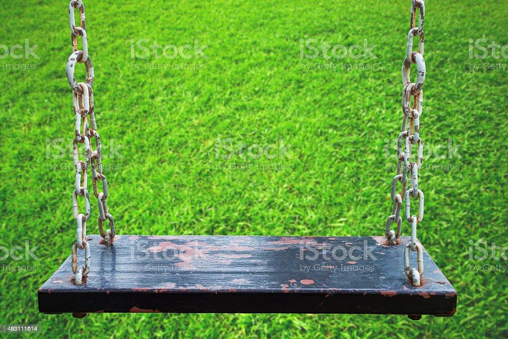 Rusty wood swing in meadow. royalty-free stock photo