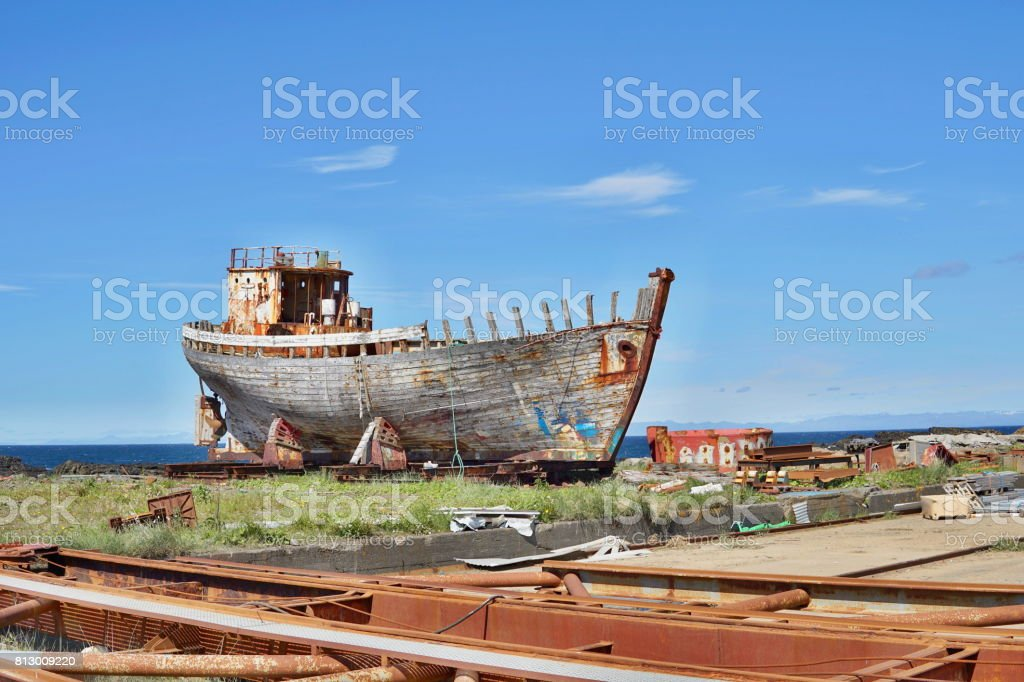 Rusty wooden and metal shipwreck in the Icelandic dry dock in the Akranes town as a symbol of corrosion and decay stock photo