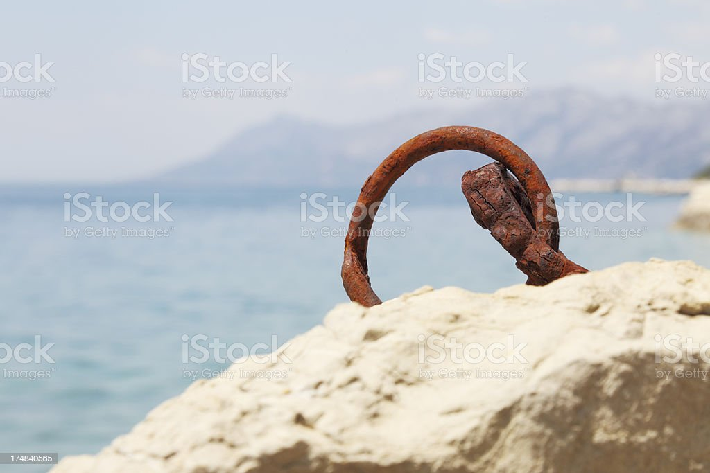 rusty worn out ship dock metal ring against ocean royalty-free stock photo