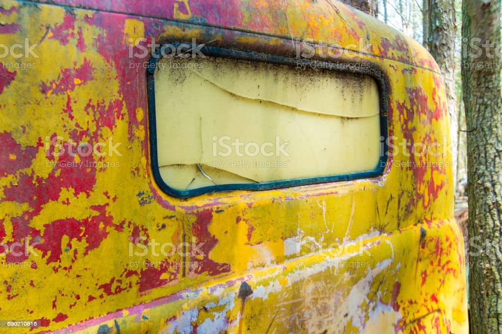 Rusty yellow paint on the back of old antique truck. stock photo