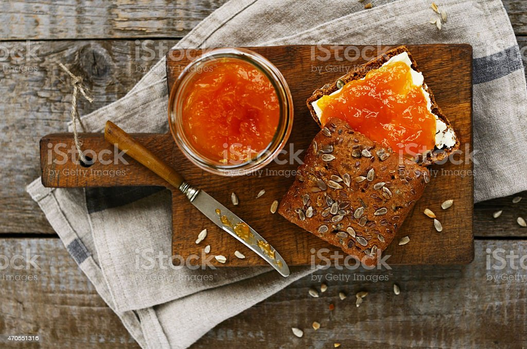 Rye bread and apricot jam sandwich on cutting board stock photo
