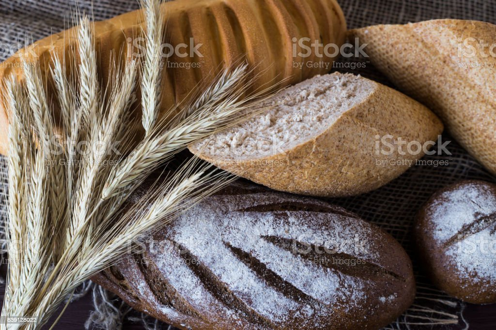 Rye, grain and white bread next to the spikelets of rye on a wooden table stock photo