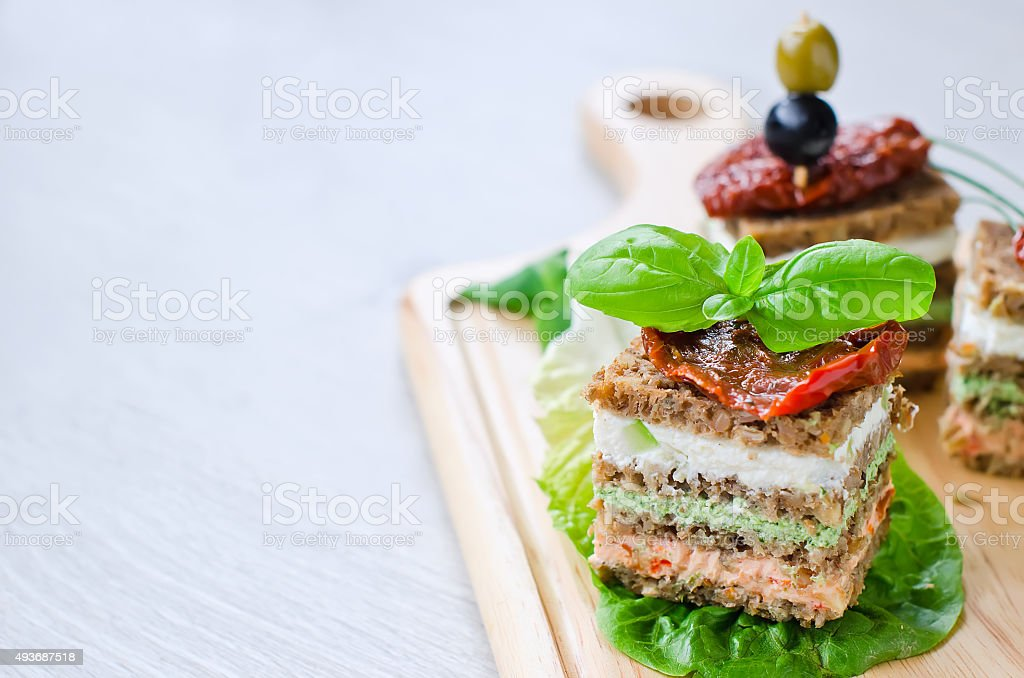 Rye granary bread sandwich cake with curd and antipasto stock photo