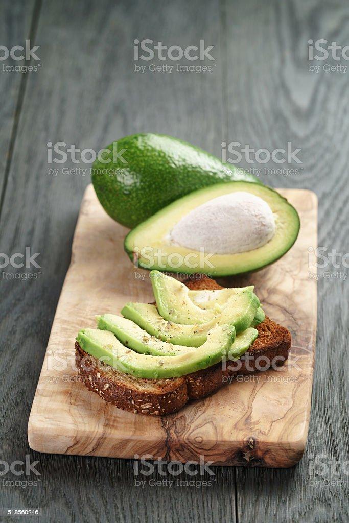 rye toast with sliced avocado and herbs stock photo